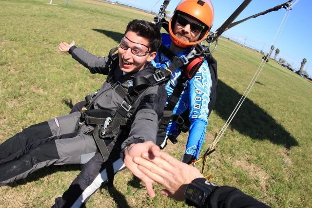 Tandem student smiling as he comes in for landing and high-fives spectator on the ground.