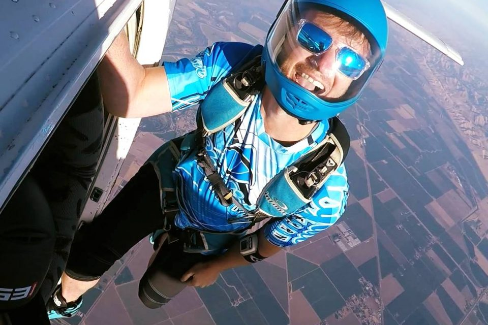 Experienced skydiver hanging off of Skydive California air craft