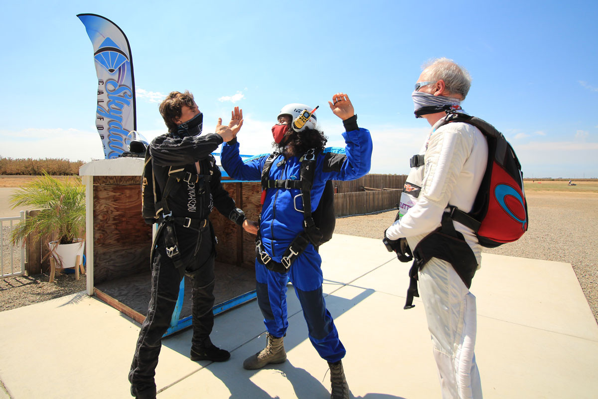 Man in blue skydiving gear learning on the ground AFF training at Skydive California.
