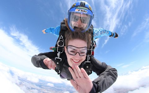 Skydive California tandem skydiver smiling and waving during free fall