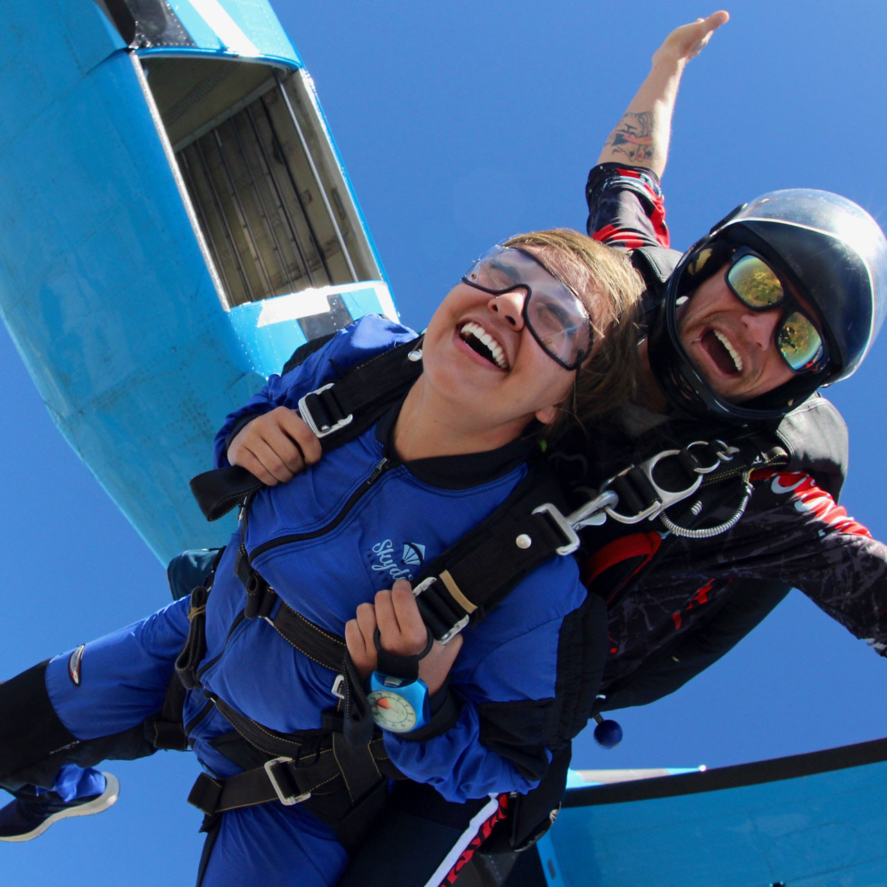 Female tandem skydiver taking the leap from the Skydive California air craft.