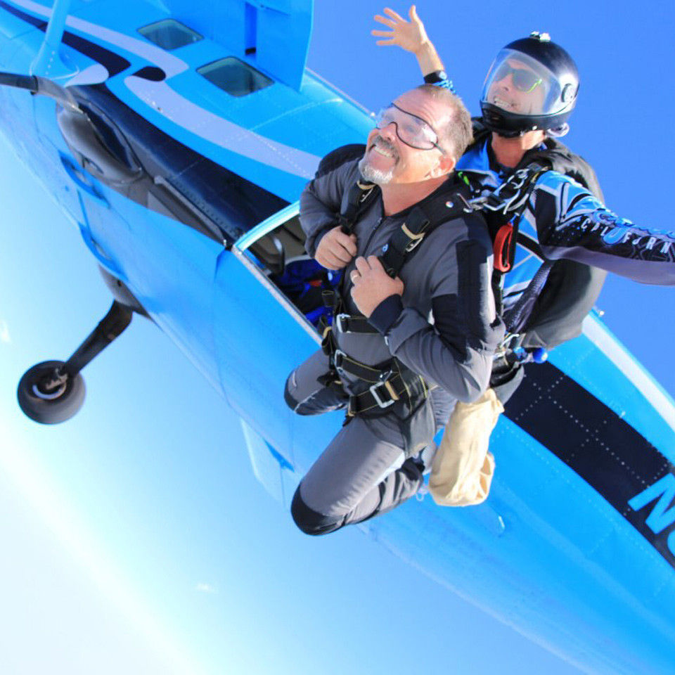 Male tandem jumper leaping from plane at Skydive California.