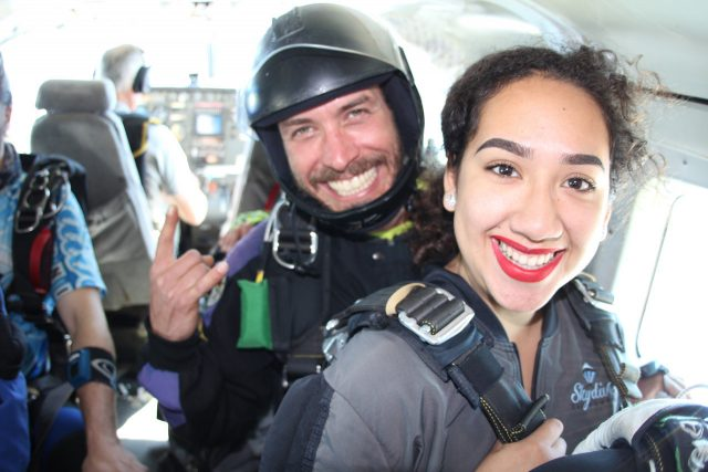Female tandem skydiver smiling in the air craft before skydiving.