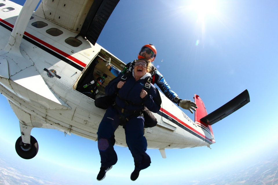 Female tandem jumper leaps from Skydive California air craft.