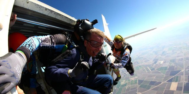Male tandem skydiver leaping out of Skydive California aircraft with instructor.