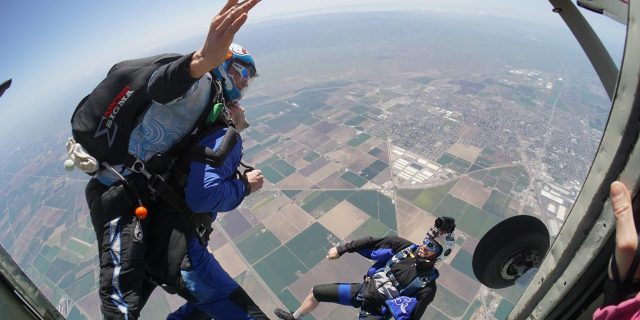 Tandem student and instructor leaping out of Skydive California airplane.