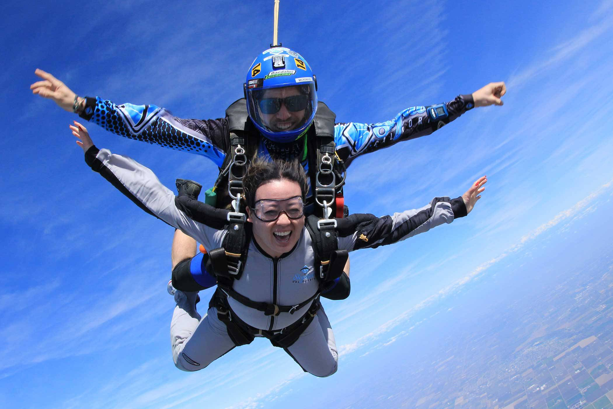 Tandem skydiver smiling from the excitement of free fall