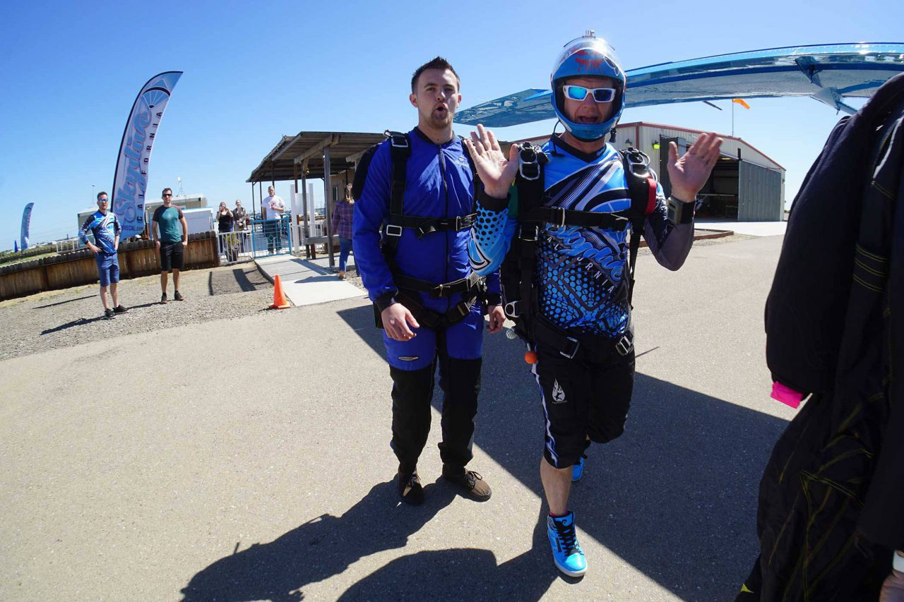 Tandem instructor and skydiver walking towards the Skydive Cal airplane.