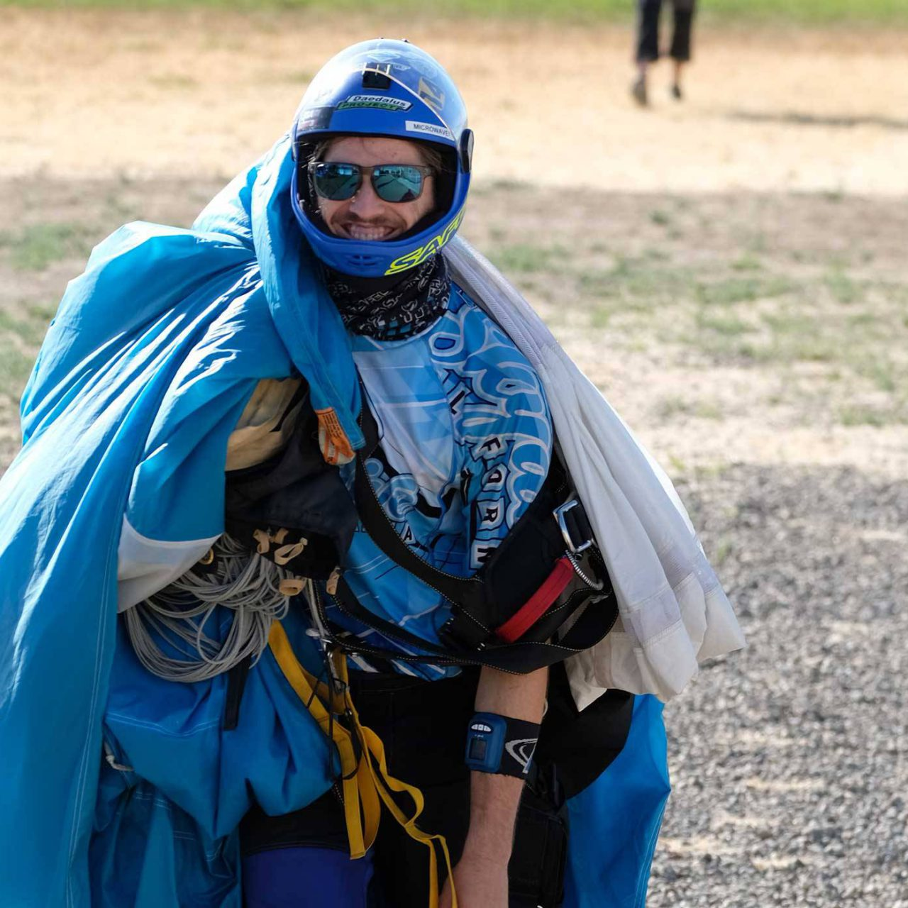 Skydiver walking with canopy in hand after jumping