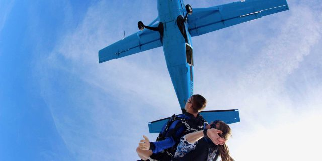 Tandem skydiver in free fall after leaping from Skydive Cal airplane