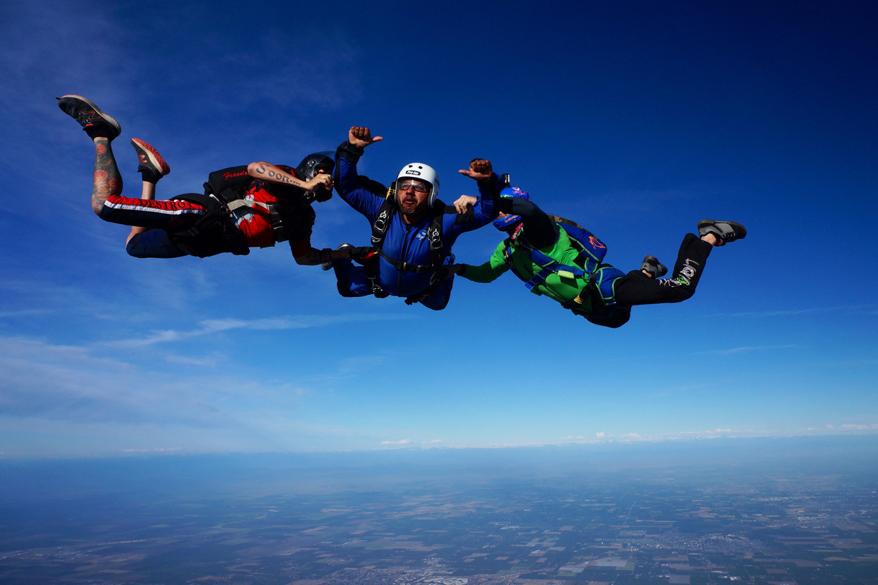 Skydive California student in free fall with two instructors.