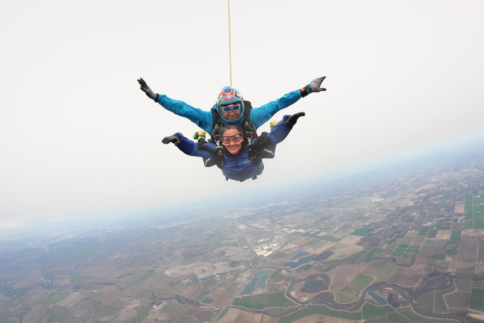 Female tandem student smiling during free fall.