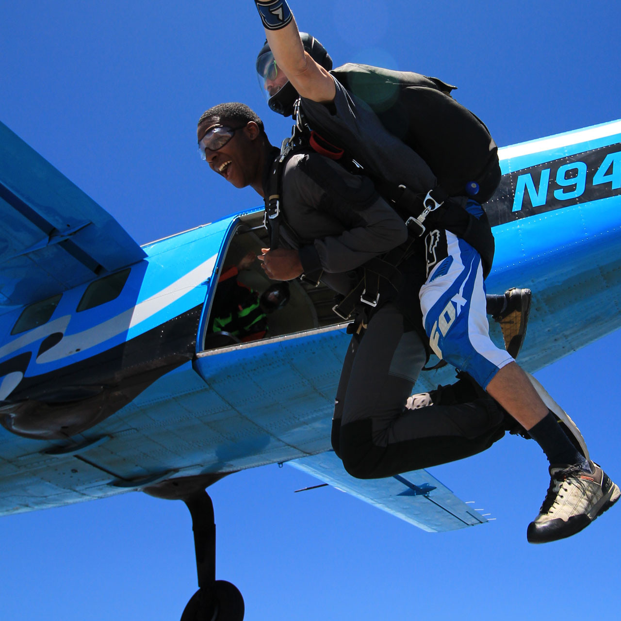 Male tandem skydiver leaping from Skydive California air craft.