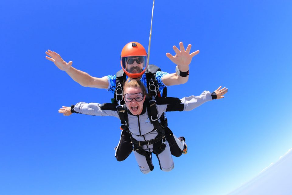 A lady spreads her arms wide and smiles while making a tandem skydive.